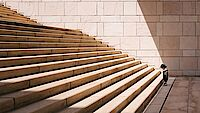 toddler standing in front of beige stair